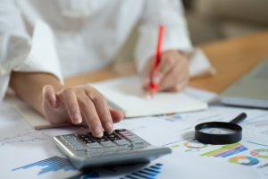 calculate,finance,accounting,Business people analyzing investment charts with calculator